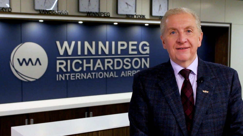 WAA President and CEO Barry Rempel poses in front of a Winnipeg Richardson International Airport sign.